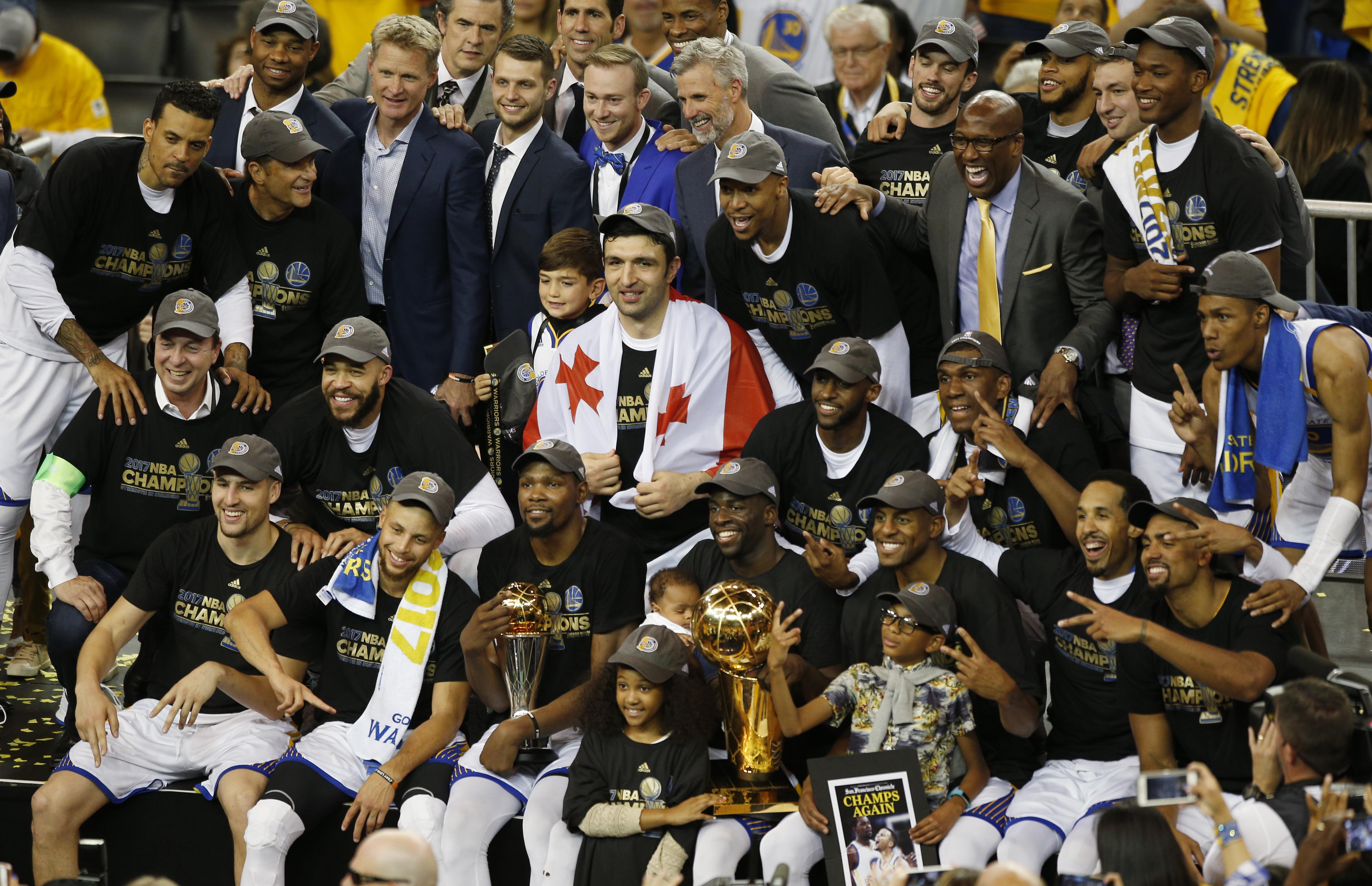 428dbfaa553 ... Golden State Warriors players and staff pose with the Larry O Brien  Trophy after defeating the Cleveland Cavaliers in game five of the 2017 NBA  Finals ...